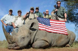 group of hunters doing a selfie with the Rhino they killed