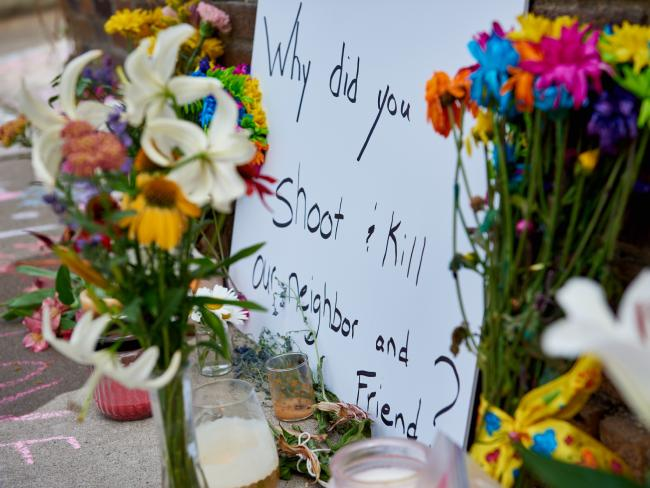 "street memorial with flowers and sign saying ""Why did you shoot and kill our neighbor and friend?"""