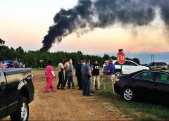 Emergency officials respond to the site of a military plane crash near Itta Bena, Miss.,