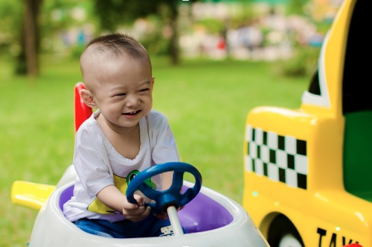 toddler in pedal car having a great time and smiling