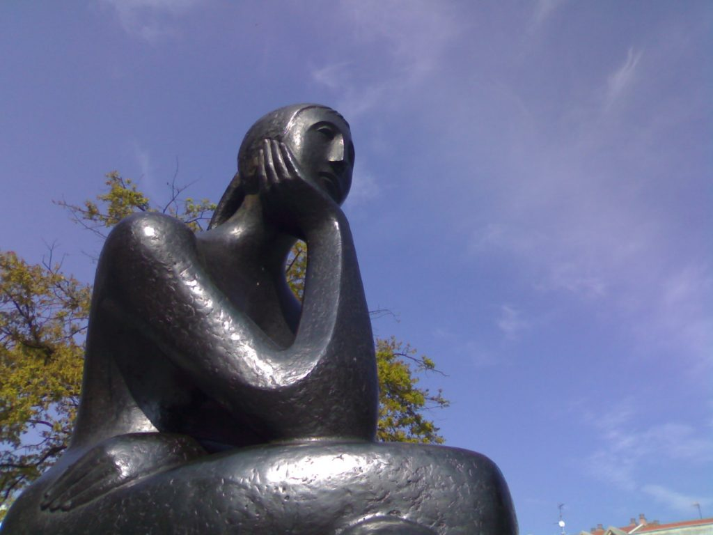 bronze statue of a woman in thought