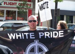 "a white supremacist / white nationalist member of the ""Aryan Guard"" holds a ""White Pride"" flag with black background and white lettering and logo"