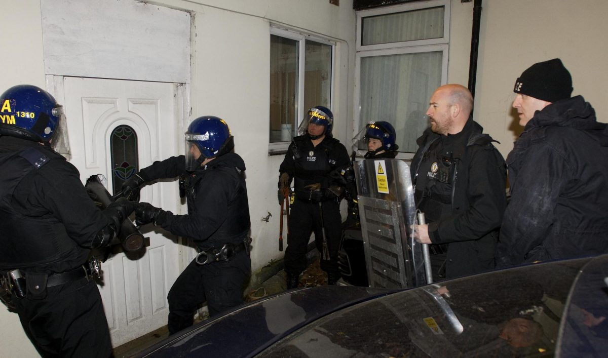 photo of a narcotics team with SWAT gear conducting a morning raid on a suspected drug ring's home