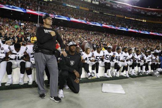 Oakland Raiders sideline - players sitting and kneeling during patriotic observances