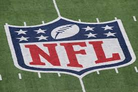 the NFL logo painted on the football field playing surface
