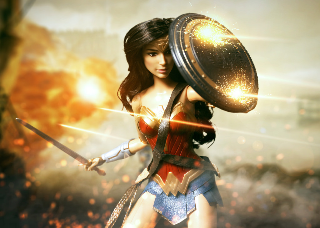 computer generated action figure of Wonder Woman with shield deflecting bullets