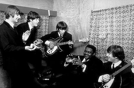 photo from 1964 of the Beatles reuniting with Fats Domino, whom they originally met in 1962 in Liverpool, England