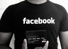 man in Facebook T-Shirt holding White Hat debit card