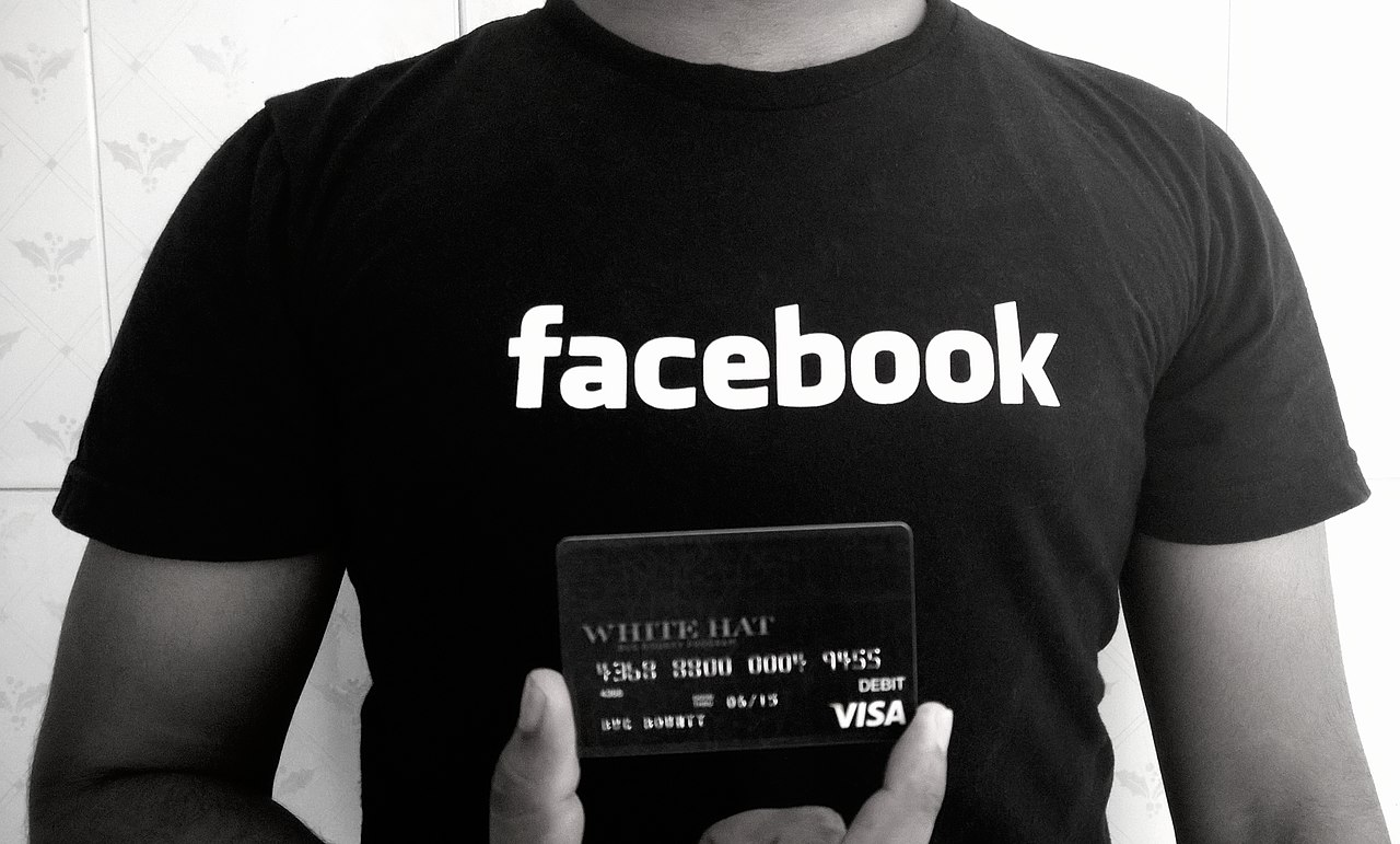 man in Facebook T-Shirt holding White Hat debit card