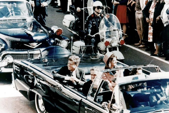 classic photo of the JFK limousine - hardtop down, completely open, with the president and his wife Jacqueline greeting crowds lining the motorcade route shortly prior to the fatal shots.