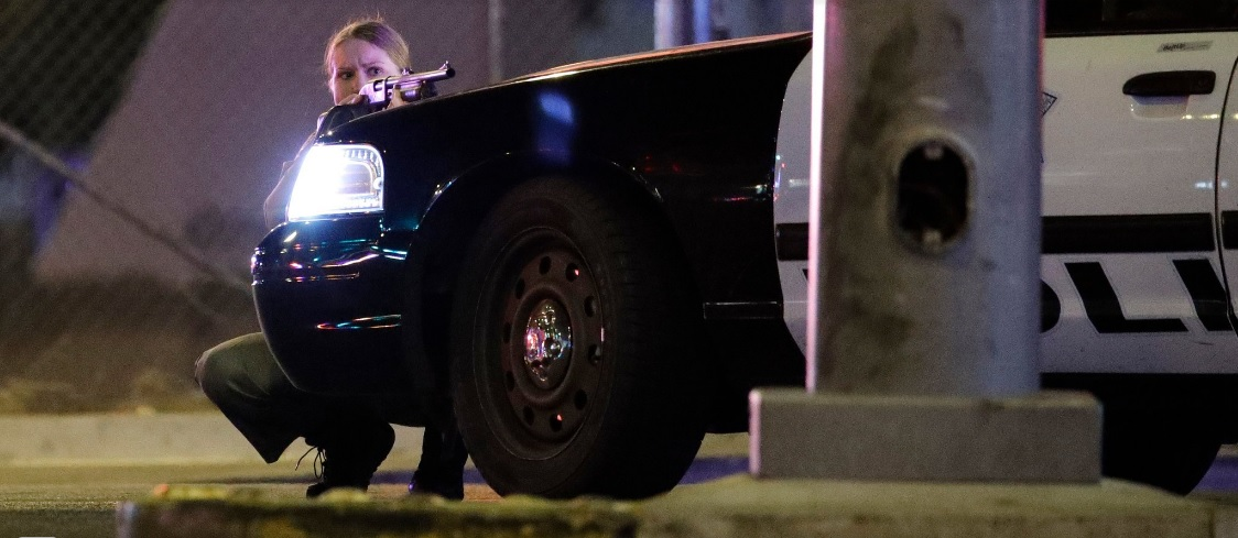 Las Vegas PD Officer taking cover behind patrol vehicle during response to mass shooting at the Route 91 Harvest Music Festival at the Mandalay Bay Hotel