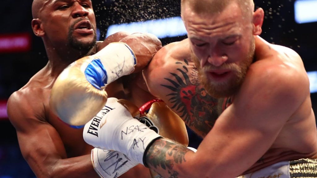 still image of Floyd Mayweather landing a hard punch on Conor McGregor in recent bout in Las Vegas