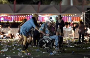 concert goers assisting elderly man to evacuate mass murder scene at the Mandalay Bay Hotel in Las Vegas