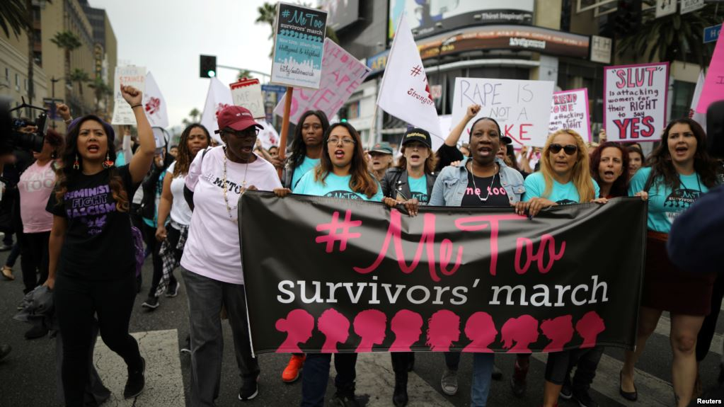 "women protesting at a rally for the ""Me Too Survivors' March"" and holding a banner with that title"