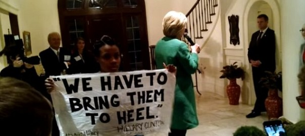 "A protester during a speech by presidential candidate Hillary Clinton holds sign reminding attendees of Clinton's ""Superpredators"" comments about black gang members, ""we have to bring them to heel"""