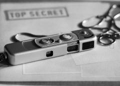 "photo of cold war era Minox miniature spy camera sitting on top of a folder marked ""Top Secret"""