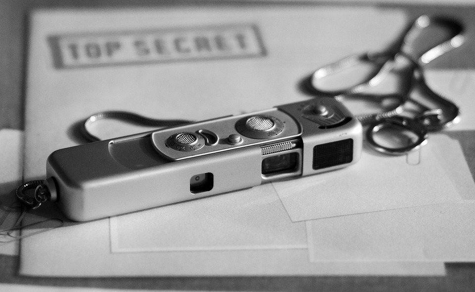 "photo of cold war era Minox miniature spy camera sitting on top of a folder marked ""Top Secret"""
