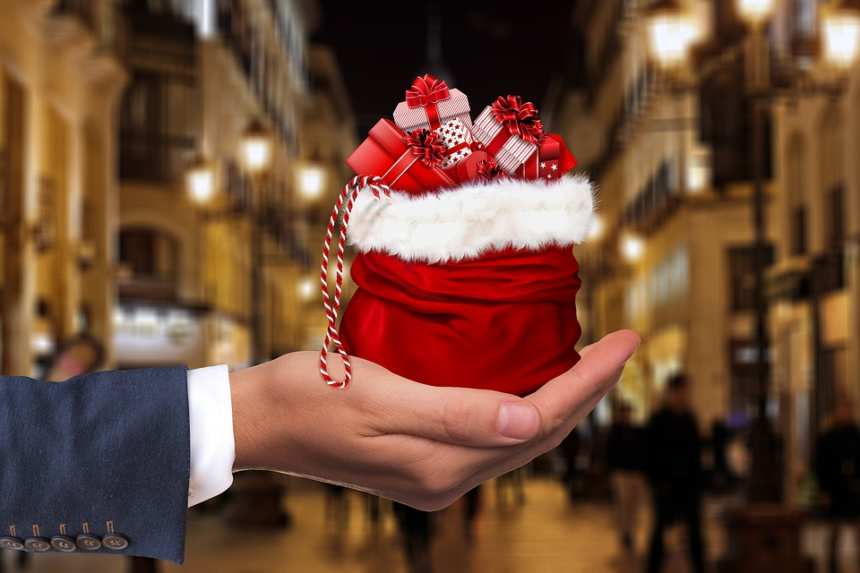 photo image of hand offering Christmas stocking brimming with gifts to an individual not seen in image