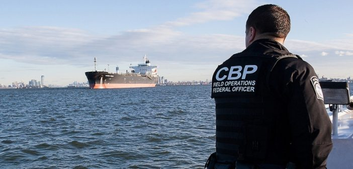image of Customs and Border Patrol officer on duty observing an oil tanker off the coast.