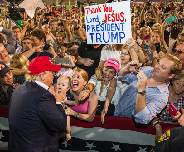 Trump rally attendees displaying fanatical devotion to Trumps as to a religious icon
