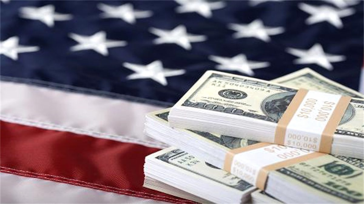 photo of American flag laid out flat and stacks of $100 bills piled on top of it