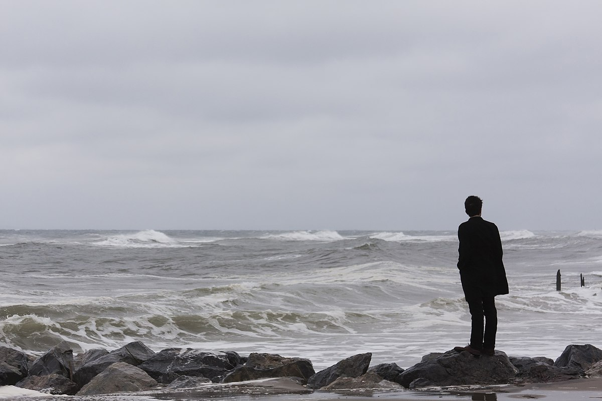 photo of a man standing on a rocky beach looking at waves breaking out in the ocean. Photo portrays solitude and loneliness.