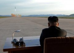 photo from North Korea news agency, of Kim Jong-Un sitting at desk on the tarmac of a missile launch site witnessing a missile test launch.