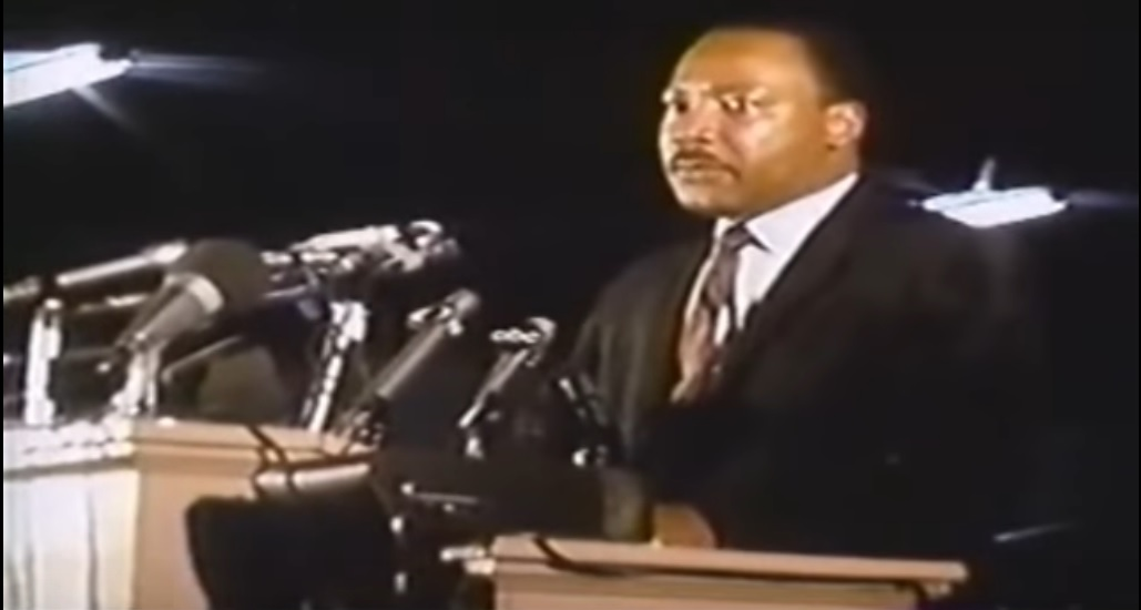 "video still of the Reverend Martin Luther King delivering his ""I have been to the Mountaintop"" oration in Memphis on April 3, 1968"
