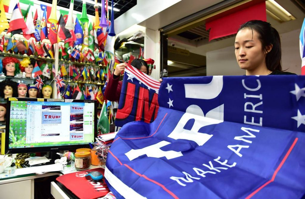 Chinese worker folds Trump campaign flag -displaying the contradiction of Trump's Trade War rhetoric.