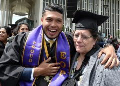 A third-generation immigrant student graduates from university with his grandmother beside him.