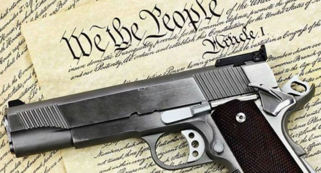 A firearm lays on top of a simulation of the U.S. Constitution.