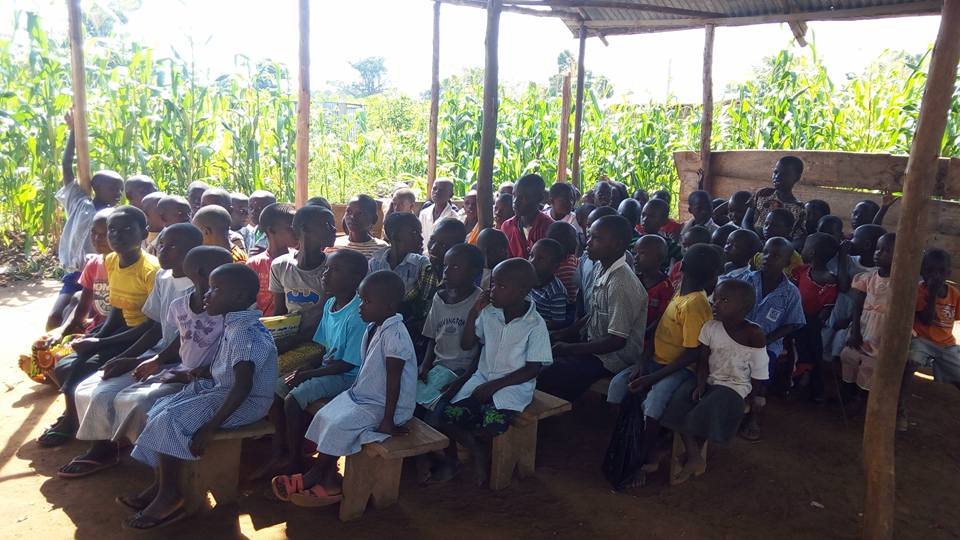 School children at Neema Mission Centre attending classes in the shade of a temporary assembly area because severe storms decimate makeshift campus buildings.