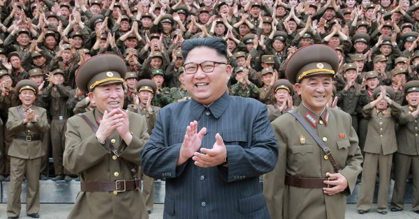 image of North Korean authoritarian head of state Kim Jong Un in the company of thousands of DPRK military personnel including top army brass.