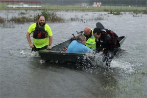 Volunteers rescue a disable man from flood waters.