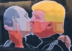 photo of well known graffiti of Vladimir Putin and Donald Trump kissing on wall of business in Vilnius, Lithuania