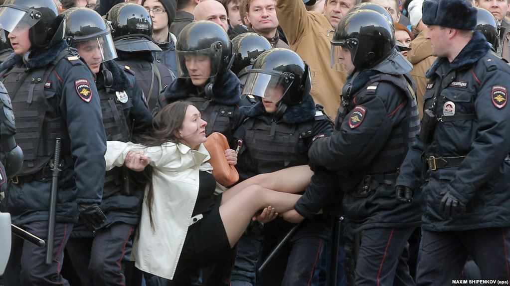 Russian police arrest protester.