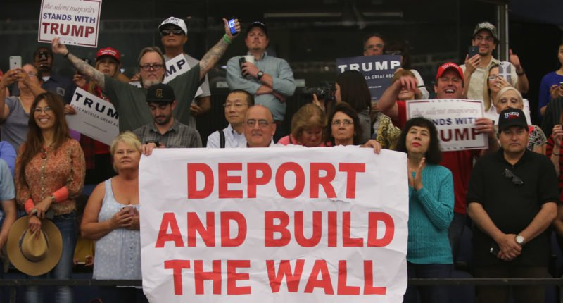 image of Trump campaign rally with supporters holding signs demanding deportation of undocumented immigrants and construction of a wall