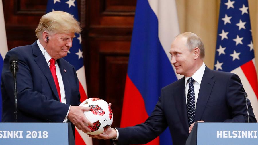 Putin gives Trump a soccer ball.