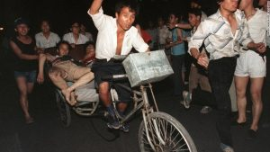 Injured man on bike in Tiananmen Square.