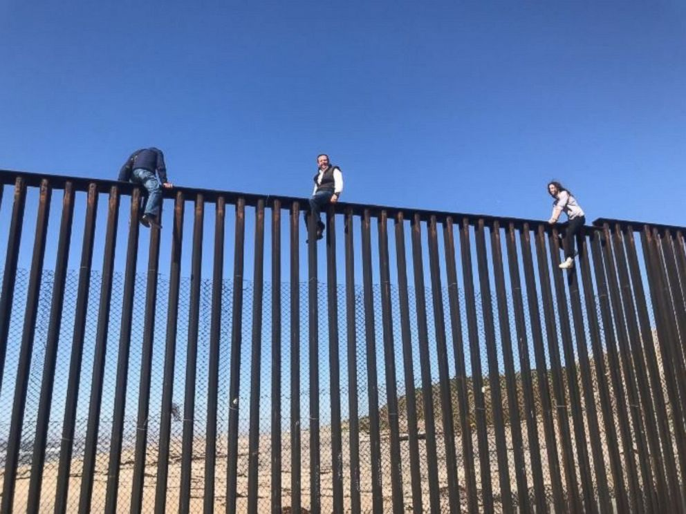 "photo of Mexican congressman and aides sitting atop vertical steel slat fencing at the U.S. Mexican border, structurally identical to the ""wall"" Donald Trump is now down selling his supporters."