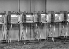 black and white photo of vintage voting stations with paper punch ballots