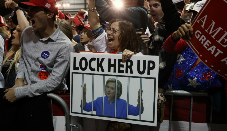 "photo of Trump rally attendees holding up signs calling for 2016 Democratic presidential nominee, Hillary Clinton to be locked up. Signs tout the phrase, ""LOCK HER UP!"""
