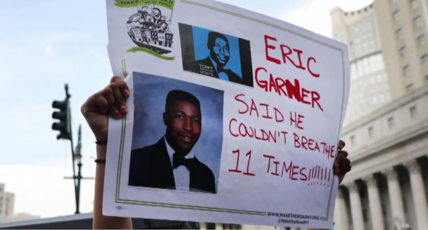 "video still of protester holding up sign, ""Eric Garner Said He Couldn't Breathe 11 Times"""