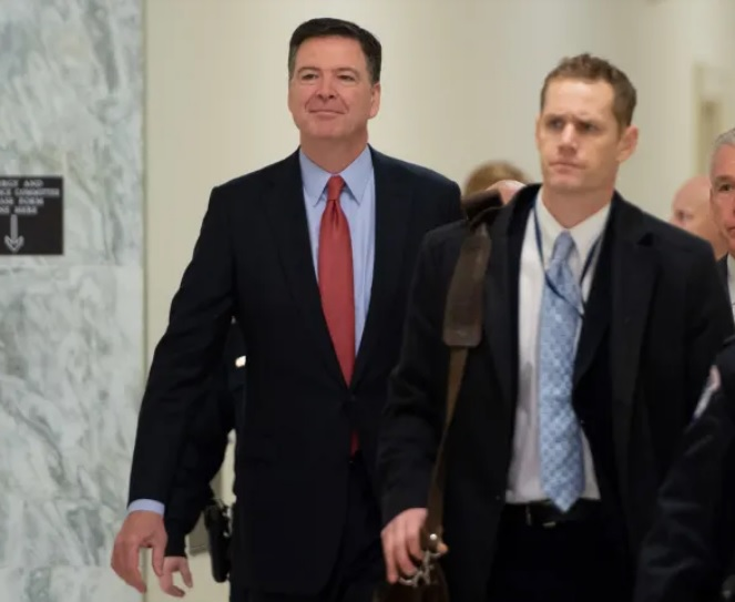 photo of former FBI Director James Comey walking through hallways leading to Congressional hearings.