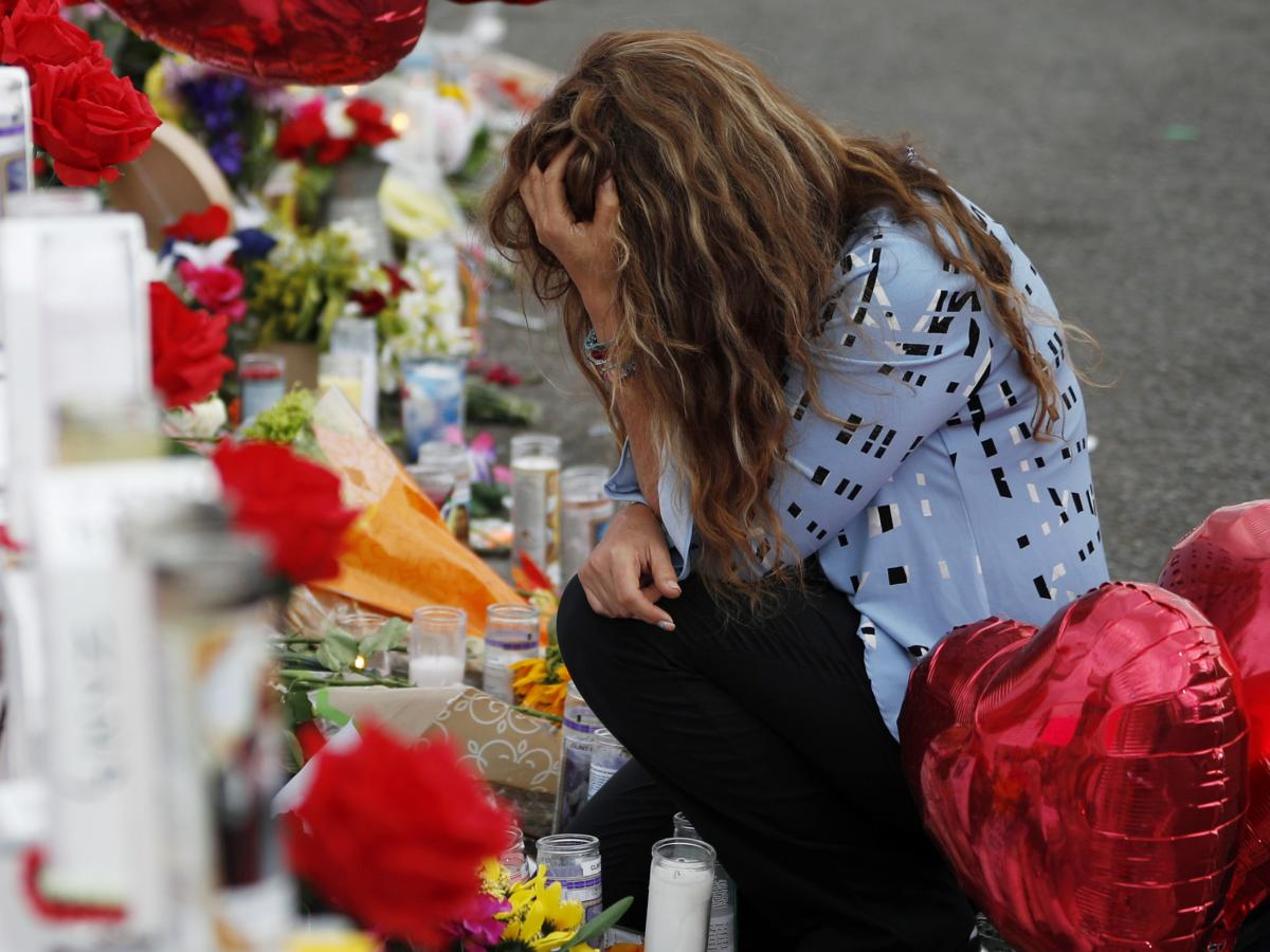Young woman kneeling at flowers left and mourning after El Paso shooting.