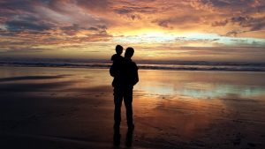 man holding his small son on the beach at sunset
