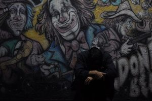 Graffiti mural of clowns and man with his head down