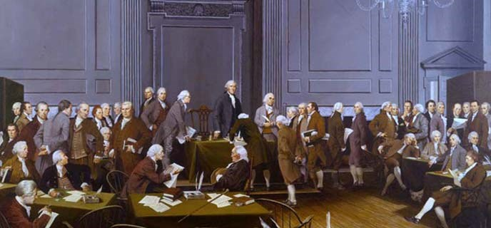 Color photo of a painting by Louis Glanzman showing the signers of the U.S. Constitution in the Assembly Room. George Washington stands at a table in the front of the room with a row of men on either side of him. A few others sit at nearby tables.