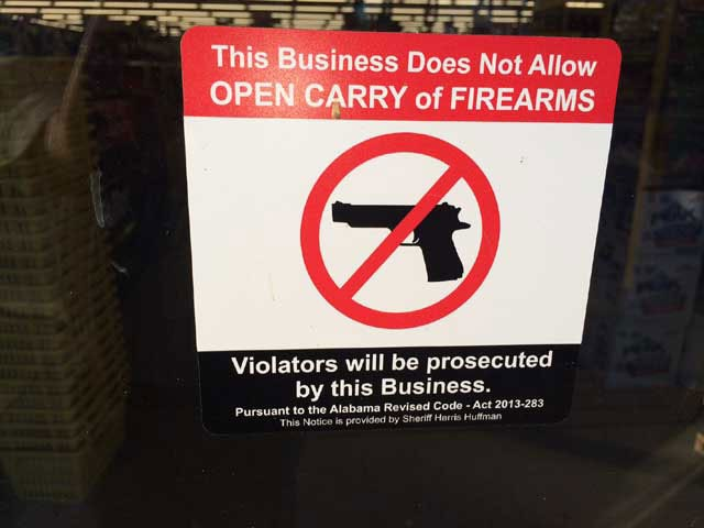 The type of signage that must be displayed at the entrance of any store in a legal open carry state in order to authorize local law enforcement to enforce trespassing laws.