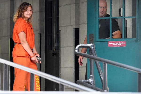 Reality Winner, Trump's first political prisoner, being taken handcuffed into federal prison.